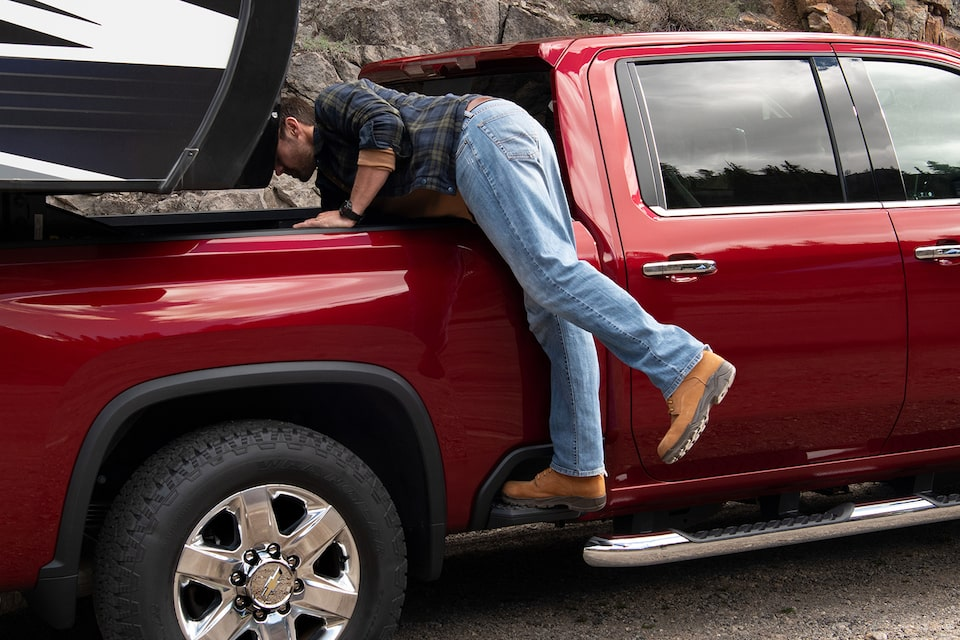 A man uses the exterior side step of the 2021 Chevy Silverado HD Truck for an easier reach to bed  storage.