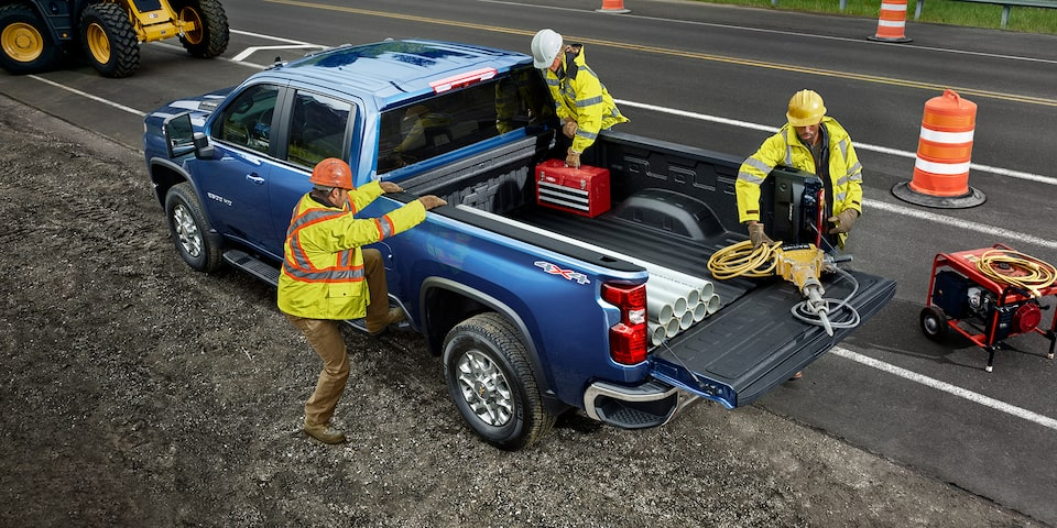 Two men using the 2021 Chevy Silverado HD Truck bed for commercial work.